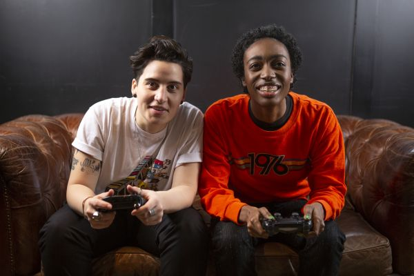 Two non binary friends playing video games laughing